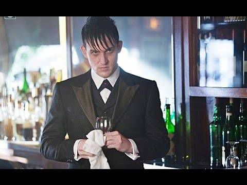 Scowling man in a tuxedo stands behind a bar, wiping a glass