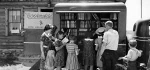 Children browse the exterior shelves of a bookmobile