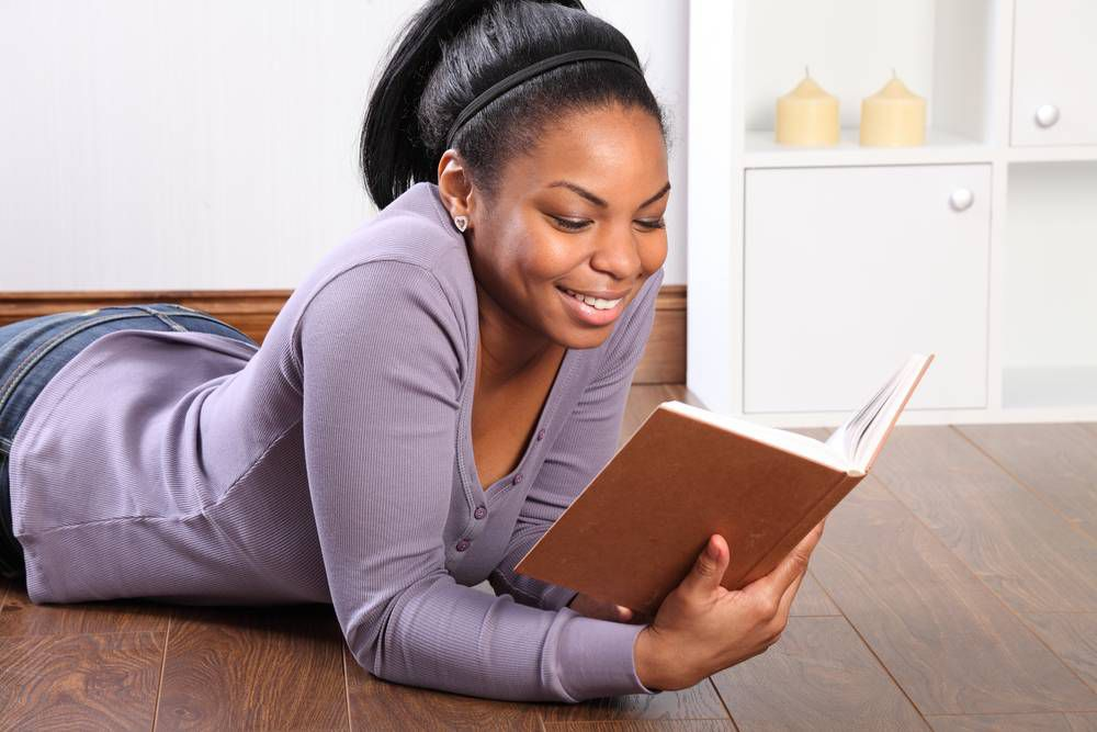 Beautiful young black girl, big smile, wearing jeans and purple top, lying on the floor at home, reading a book.