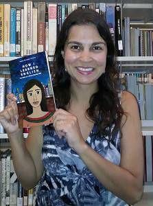 Diverse Librarian Paula Pereira holding her book