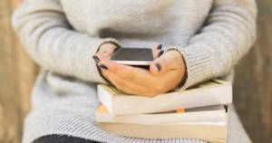 girl sitting with a cell phone and books