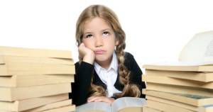 little unhappy sad student blond braided girl bored with stacked books on white background