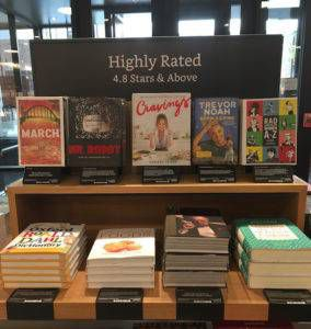 """Table displaying multiple books with a sign that says """"Highly Rated."""""""