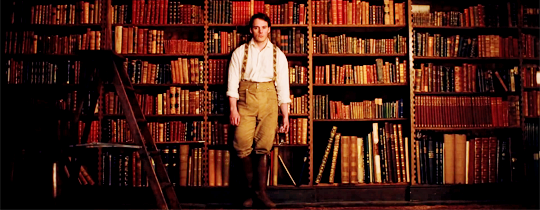 sam claflin standing in front of books in my cousin rachel