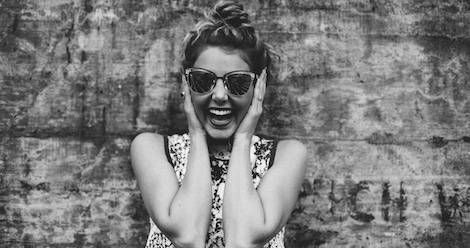 black and white photo of a girl laughing, holding her ears, wearing sunglasses