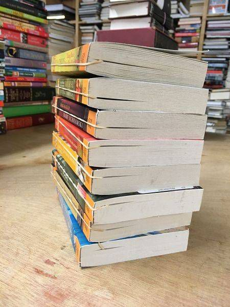 Rubber bands used as bookmarks in a stack of romance pocketbooks.