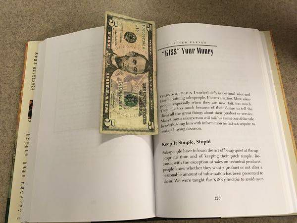 Money used as a bookmark in a Dave Ramsey book