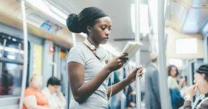 black woman reading book subway