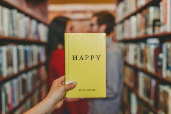 two people stand in a library behind a book entitled happy