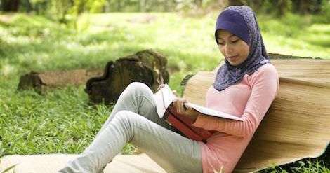 muslim woman in hijab reading a book
