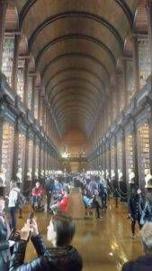 Library with high ceilings and a crowd of people taking pictures.