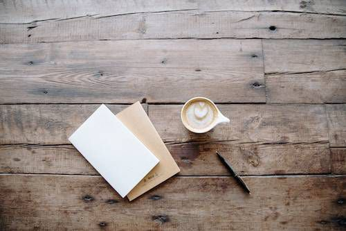 Cup of coffee, pen, and blank card and envelope on wooden table.