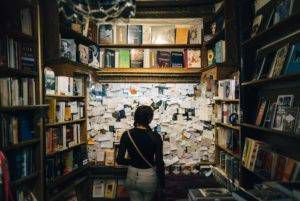 A person looks at a cork board covered in sticky notes in a bookstore.