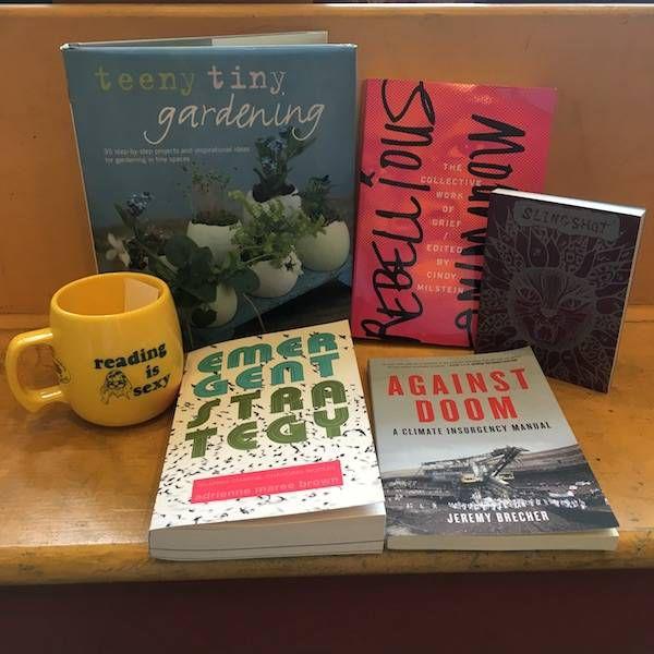 photo of four books, an organizer, and a mug