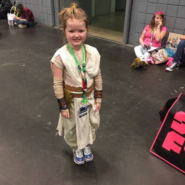 a very young girl dressed as Rey from Star Wars: The Force Awakens