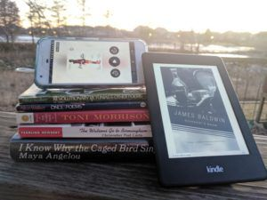 Stack of books by African-American authors listed in the article. One is on a kindle leaning against the stack, and another is an audiobook on a phone screen set on top of the stack.