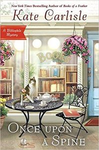 image of sidewalk cafe, table with a cat on it, chair with books, a hanging flowery plant, and a glass storefront window in background with a bookstore behind it