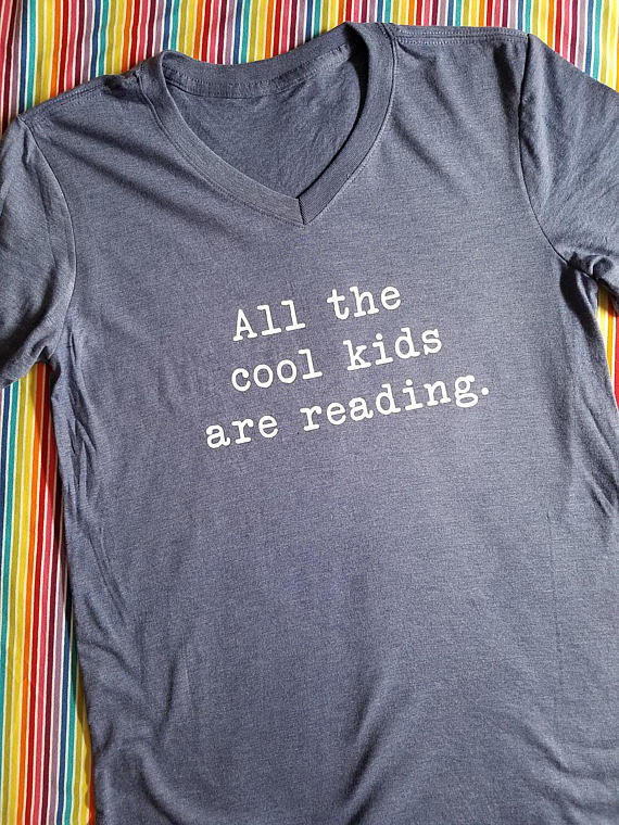"""b4dbd9c7 """"All the cool kids are reading"""" book t-shirt, $20 and up. Various colors  and sizes up to a men's 3XL."""