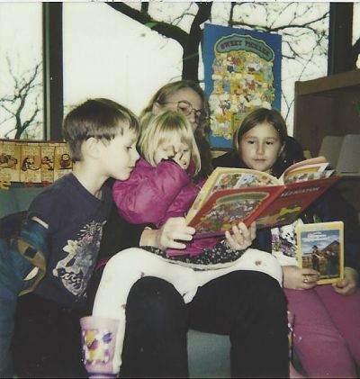 Contributor Emily Polson reads with her mother, sister, and brother at the library, shared in celebration of bookish moms for mother's day