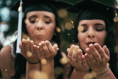 image of two new high school graduates in graduation regalia