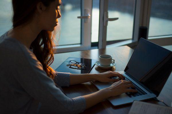 photo of woman writing on laptop