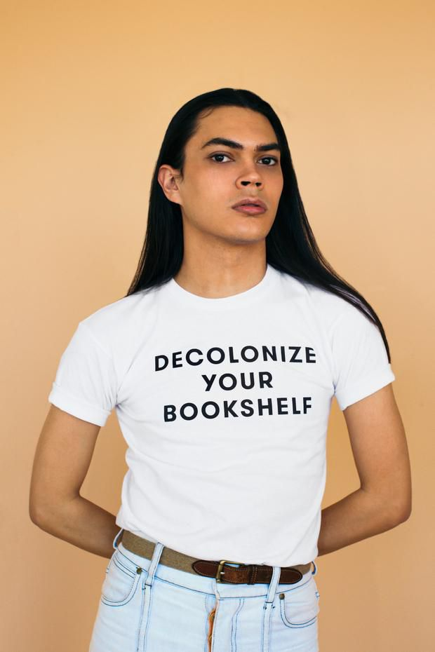 person wearing tshirt with DECOLONIZE YOUR BOOKSHELF on it