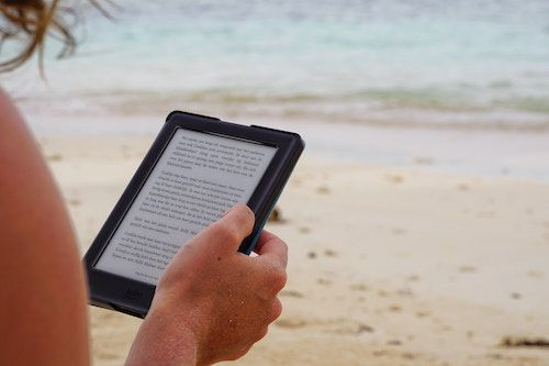 Reading a Kindle on the beach in BLEAK HOUSE on the Beach: What Makes a Good Beach Read? | BookRiot.com