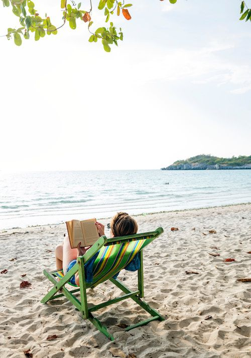 Woman reading a book on the beach in BLEAK HOUSE on the Beach: What Makes a Good Beach Read? | BookRiot.com