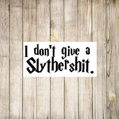 "White sticker on a wood background. Sticker has black text in Harry Potter-esque font that says, ""I don't give a Slythershit."""