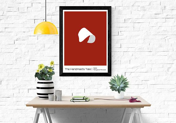 Poster hanging on white brick wall in front of a desk with several items on it. Print has a red background with a stark white Puritan-esque bonnet. Black text at the bottom of the print reads The Handmaid's Tale, 1985, Margaret Atwood