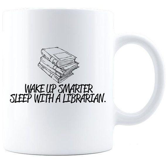 "White coffee mug with a stack of books illustrated. Under the stack, text reads, ""Wake up smarter. Sleep with a librarian."""