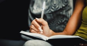 woman writing in notebook, book signings