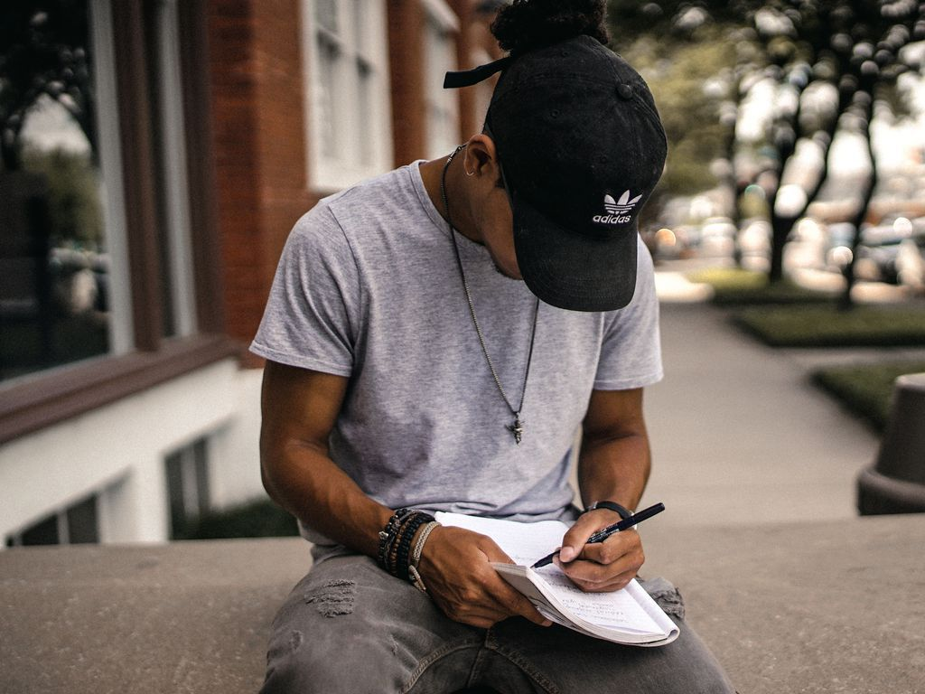 Man writing with left hand in a notebook on his lap