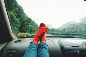 Feet on car dashboard with forest background