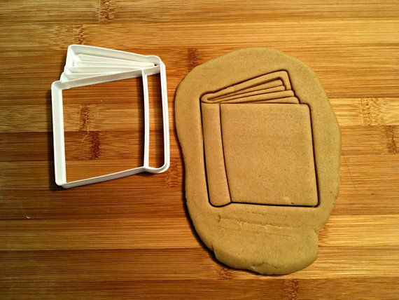 Book cookie cutter with dough and cookie cut out