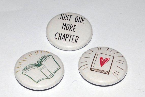 """Trío de insignias: una lectura """"Solo un capítulo más"""", una con un libro abierto y otra con un libro cerrado con un corazón en ella"""