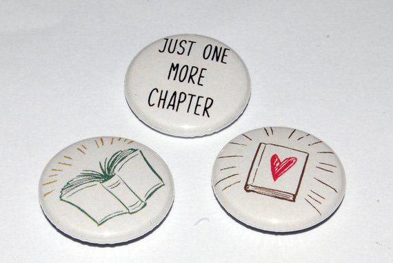 "Trio of badges: One reading ""Just one more chapter"", One with an open book, and one with a closed book with a heart on it"