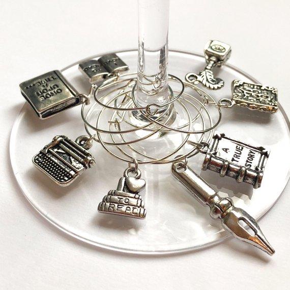 Encantos de plata con forma de libros, un bolígrafo, una máquina de escribir, etc., unidos a una copa de vino