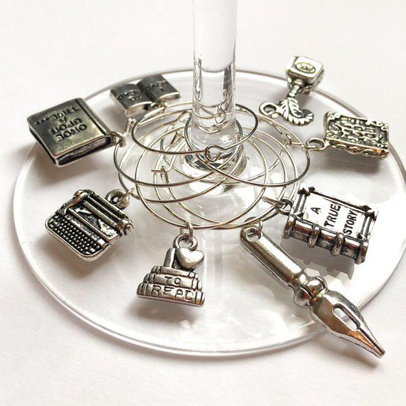 Silver charms shaped like books, a pen, a typewriter, etc., attached to a wine glass