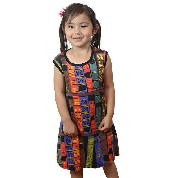 A little girl wearing a sleeveless dress printed with book spines