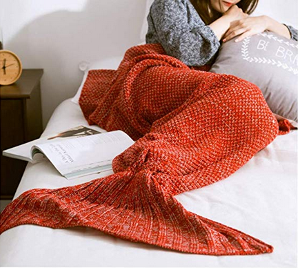 a woman with her legs inside a crochet red mermaid tail blanket while laying down
