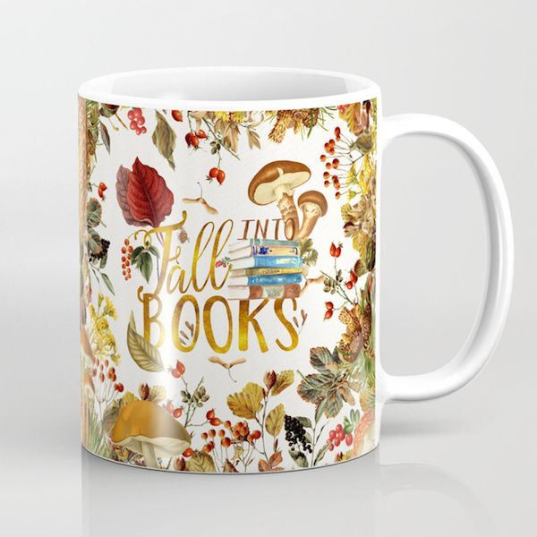 """a white mug with a graphic design of fall items including books with mushsrooms saying """"fall into books"""""""