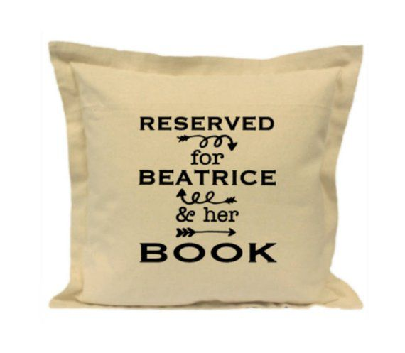 "Beige pillow that says ""Reserved for Beatrice and her Book"""