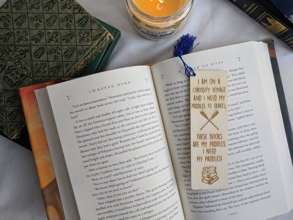 "Wooden bookmark engraved with ""curiosity voyage"" Stranger Things quote, paddles, and stack of books"