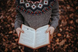 Kid Reading in the fall foliage