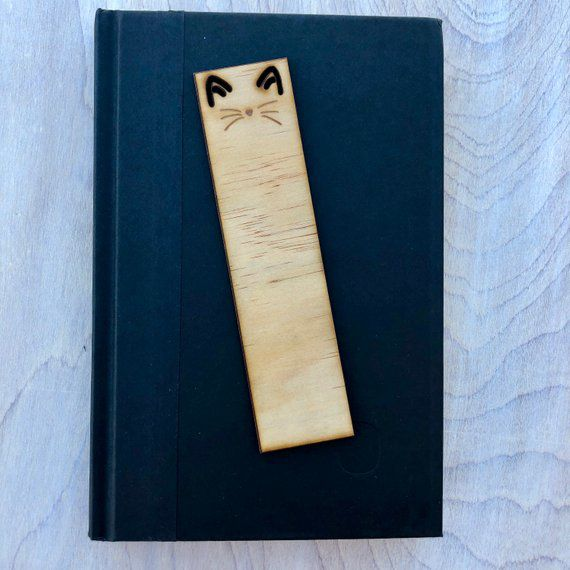 Wooden bookmark with cut out cat ears and engraved nose and whiskers