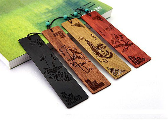 Four wooden bookmarks of different colors with traditional Chinese-style engravings
