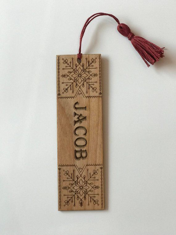 Wooden bookmark with geometric engraving on top and bottom, name in middle