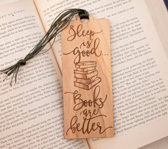 "Wooden bookmark engraved with ""sleep is good...books are better"" quote and stack of books"