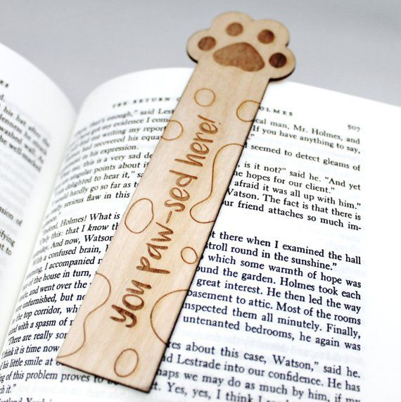 "Wooden bookmark engraved with paw print and ""you paw-sed here"""